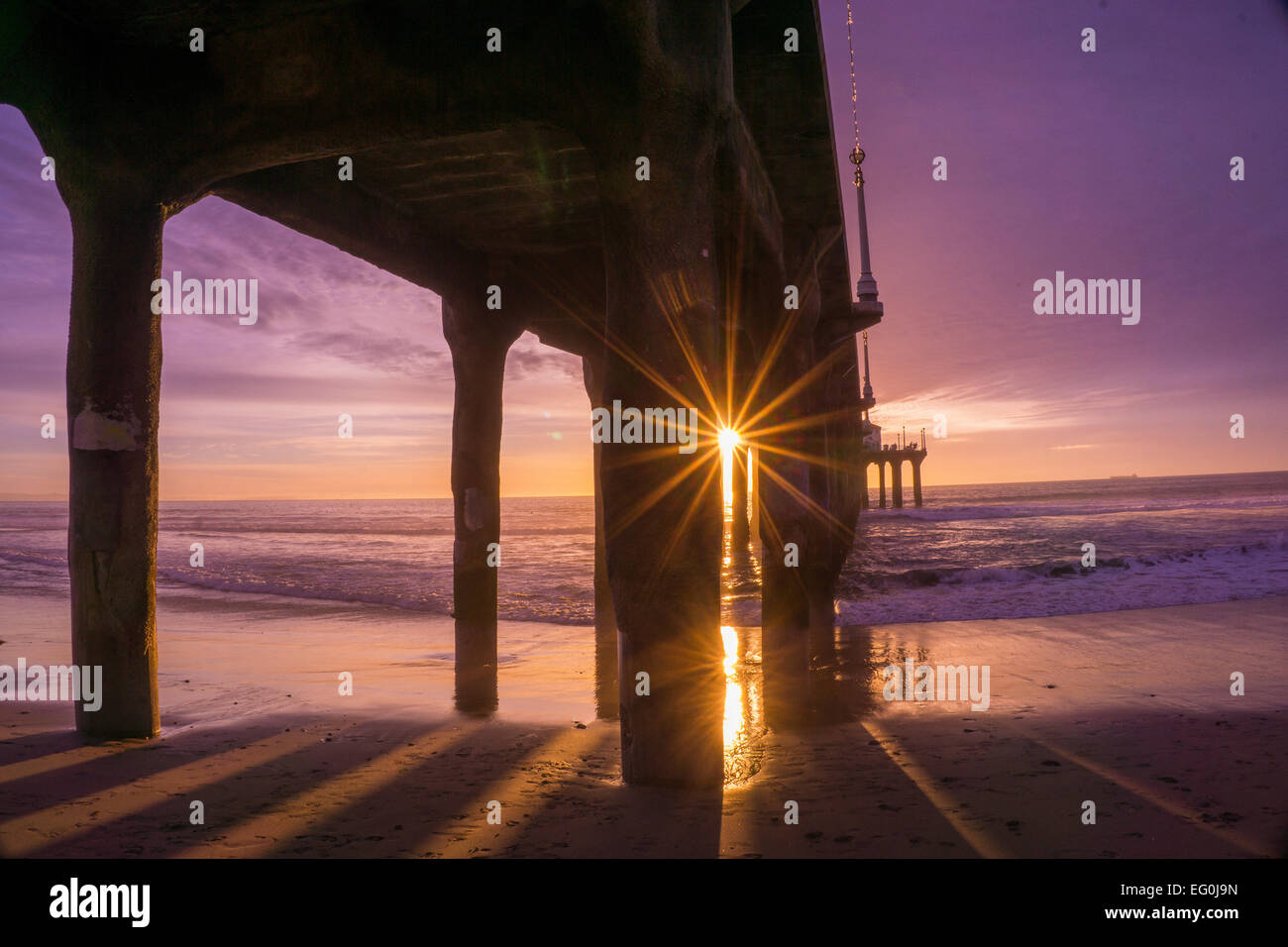 USA, California, Manhattan Beach, Sunbeam coming through pier construction, purple sky - Stock Image