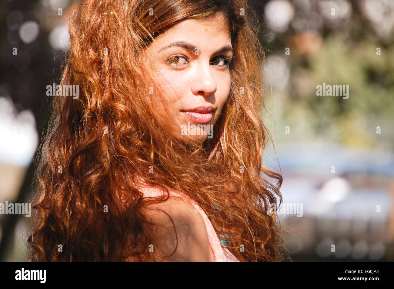 Portrait of long haired woman in sunlight - Stock Image