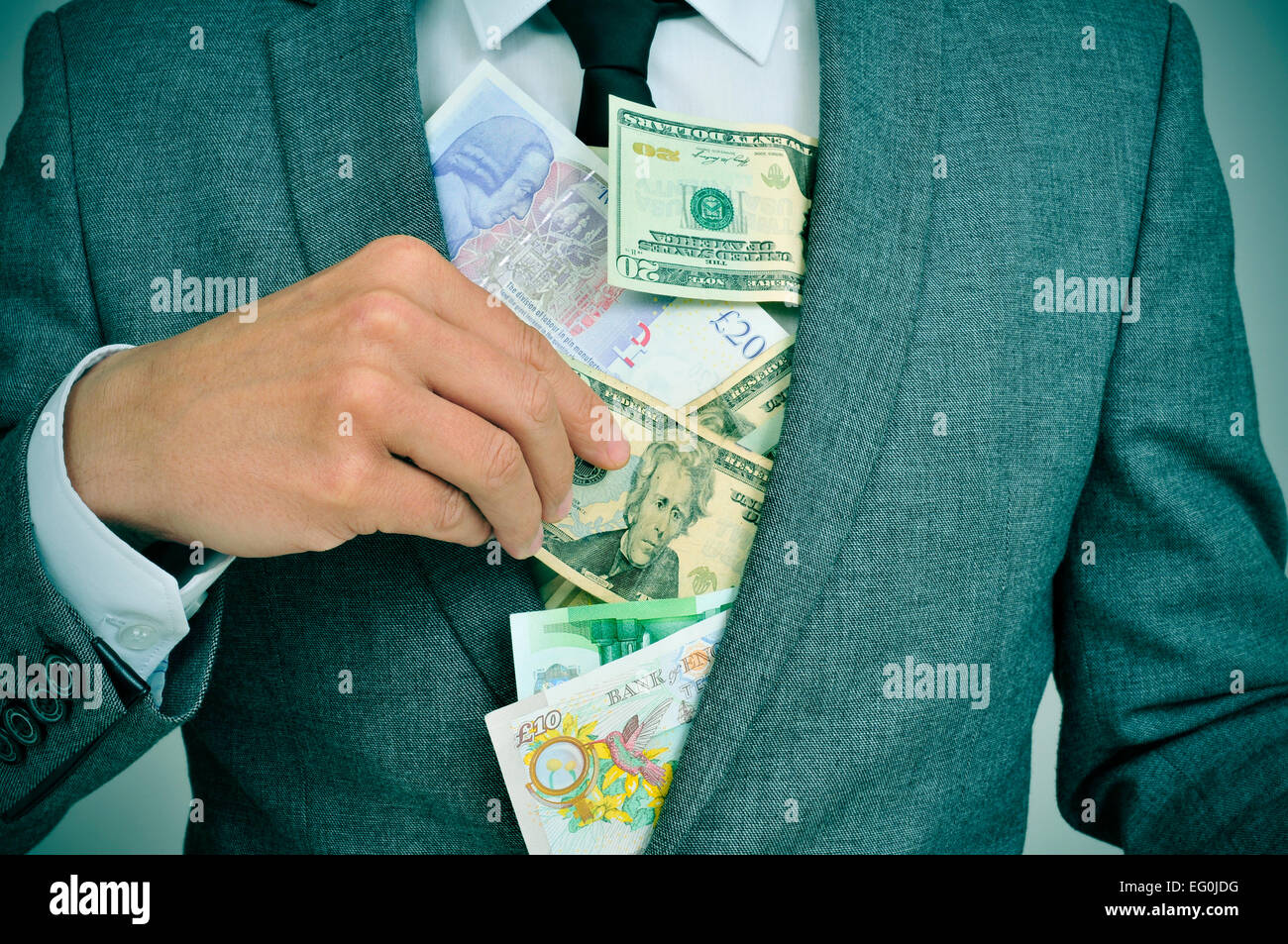 man in suit putting euro, dollar and pound bills in his jacket, depicting concepts such as greediness, corruption - Stock Image