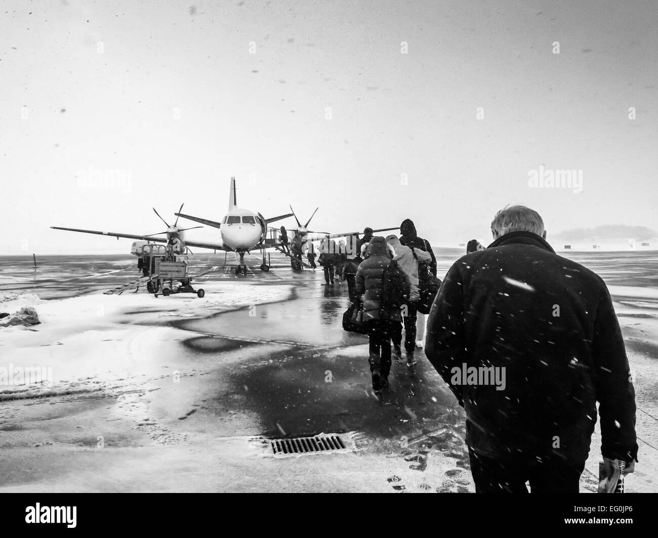 Sweden, Kalmar, Kalmar Airport, Passengers boarding small airplane in winter - Stock Image