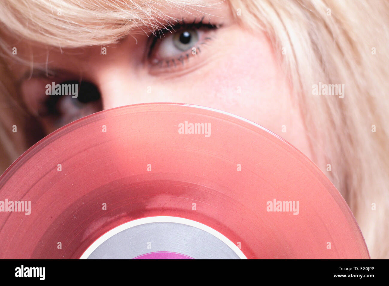 Close-up of woman hiding behind pink record - Stock Image