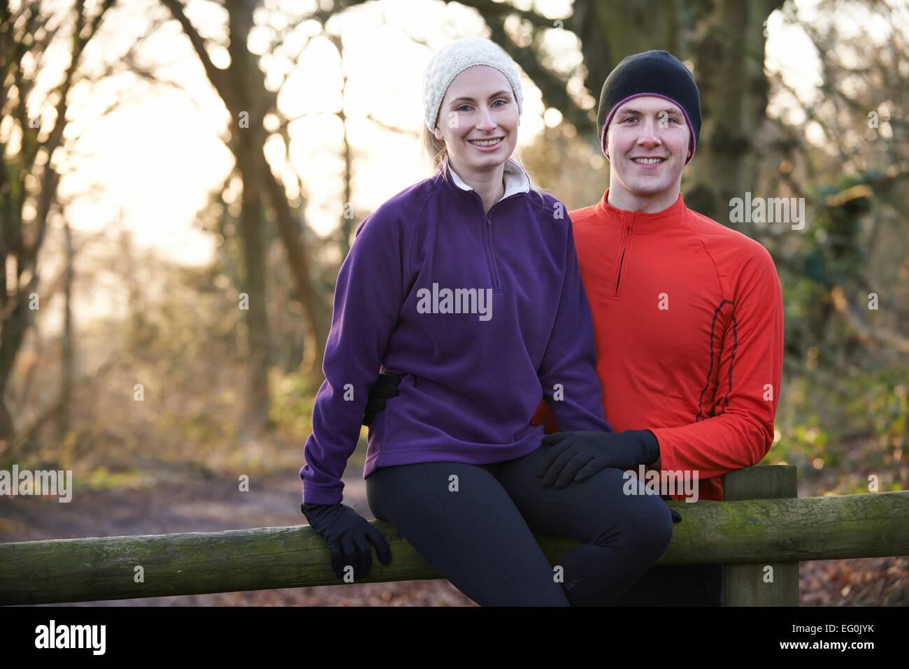 Portrait Of Couple On Winter Run Through Woodland Sitting On Fence - Stock Image