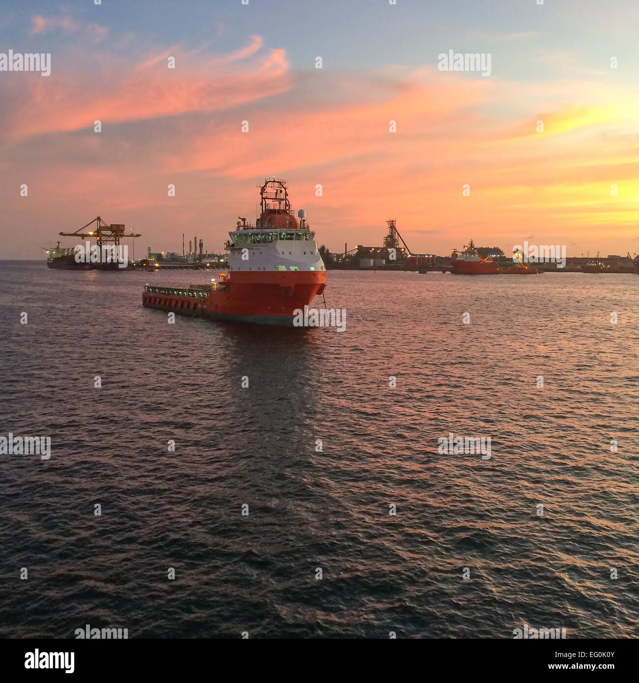 Oil rig support vessel anchored in port harbor at sunset - Stock Image