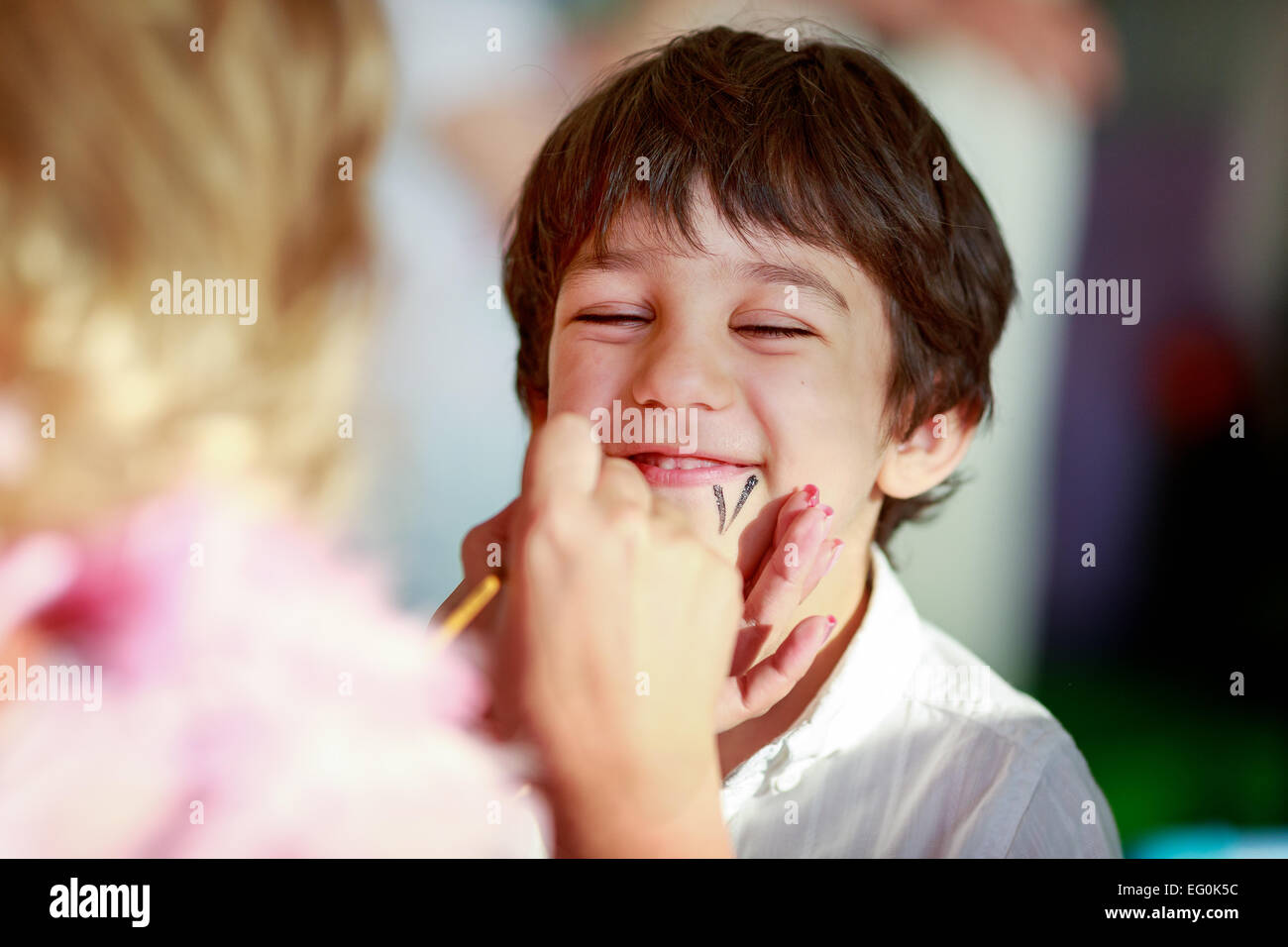 Bulgaria, Sofia, Young boy (4-5) getting his face painted - Stock Image