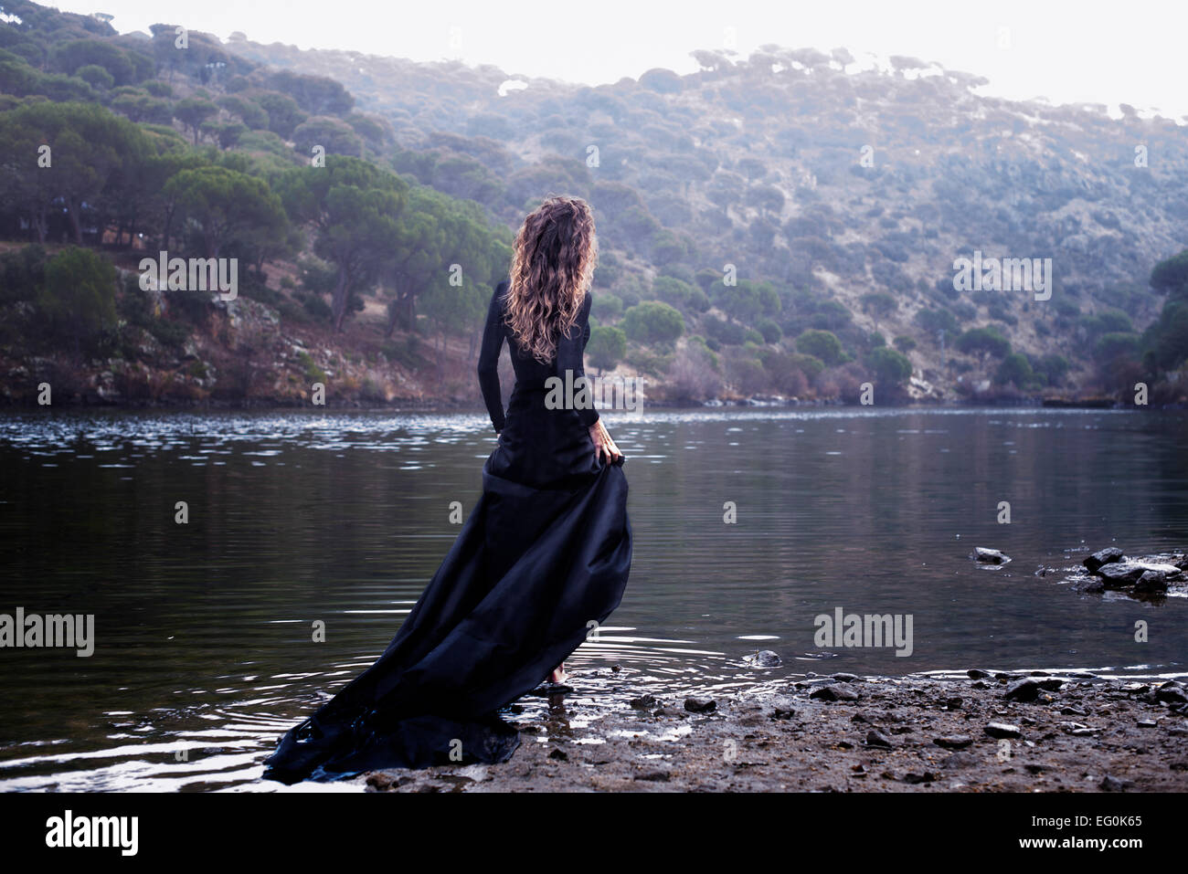 Woman in black dress walking into water - Stock Image