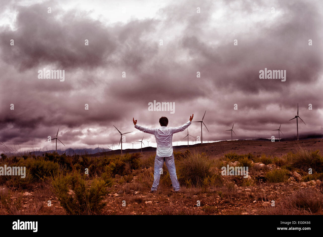 Man looking at storm clouds - Stock Image