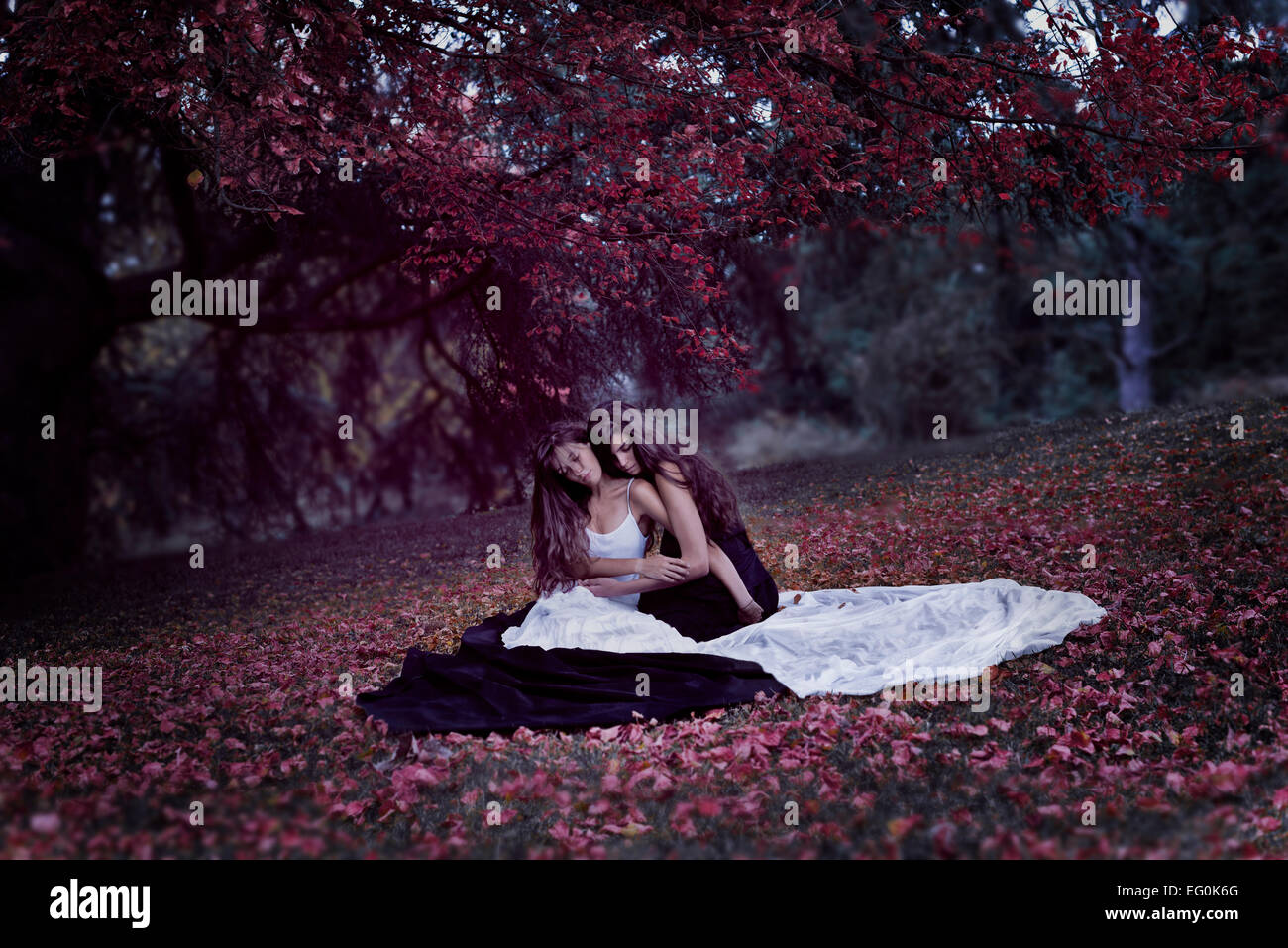 Two young women sitting on blanket - Stock Image