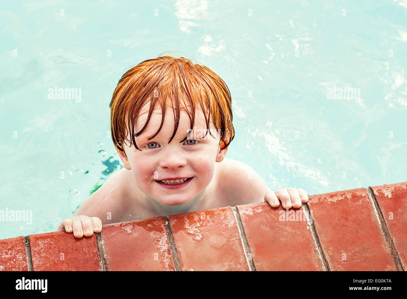 Portrait of smiling boy in a swimming pool - Stock Image