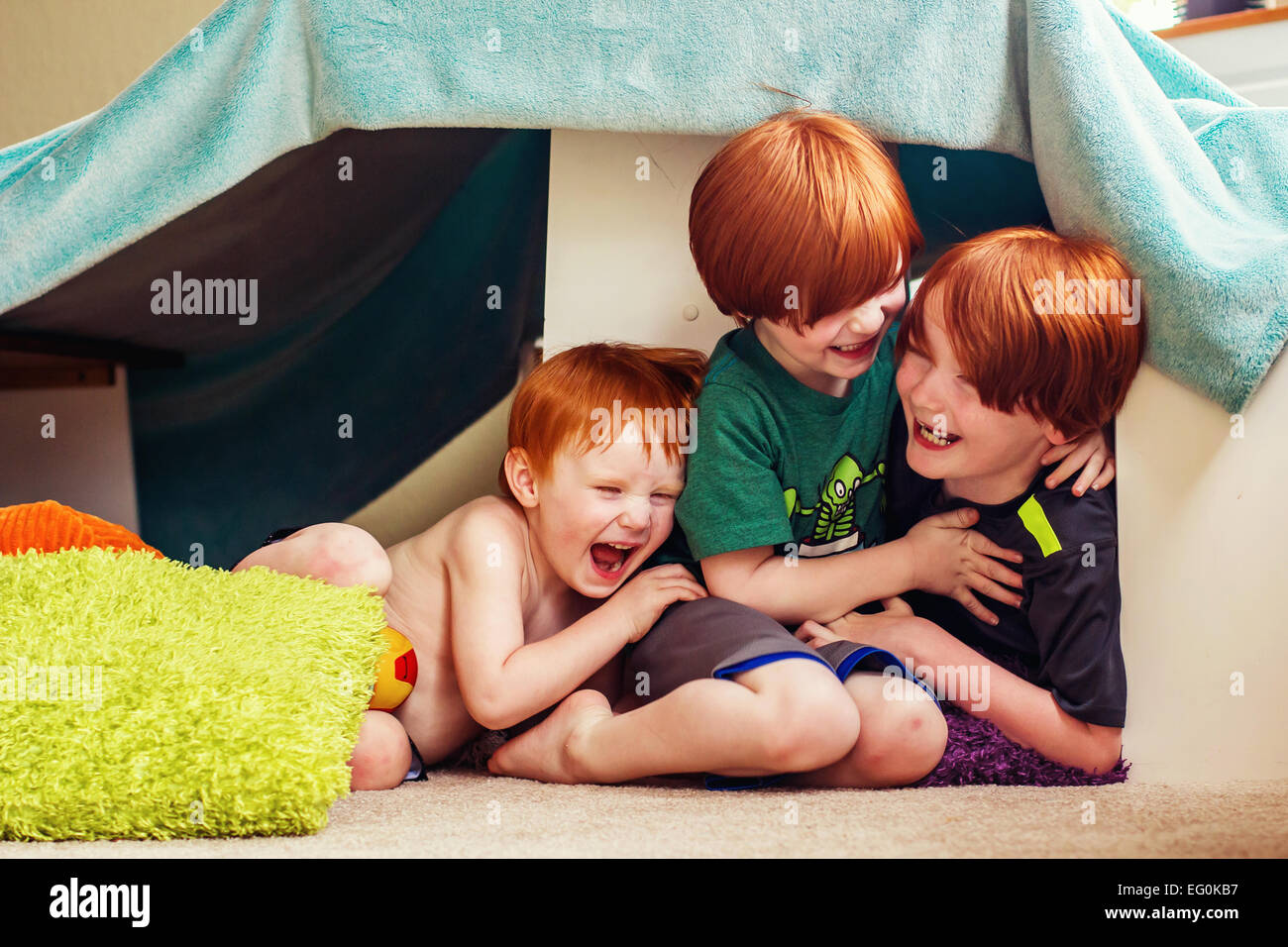 Three boys sitting in a den tickling each other - Stock Image