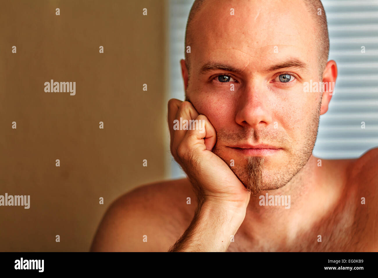 Portrait of man resting his head in his hand - Stock Image