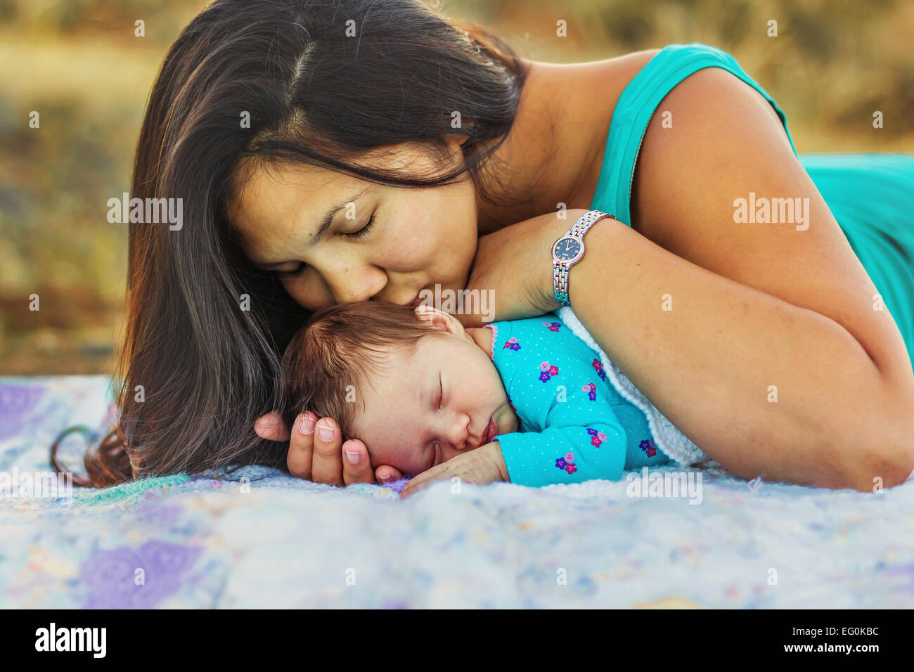 Mother kissing her newborn daughter - Stock Image