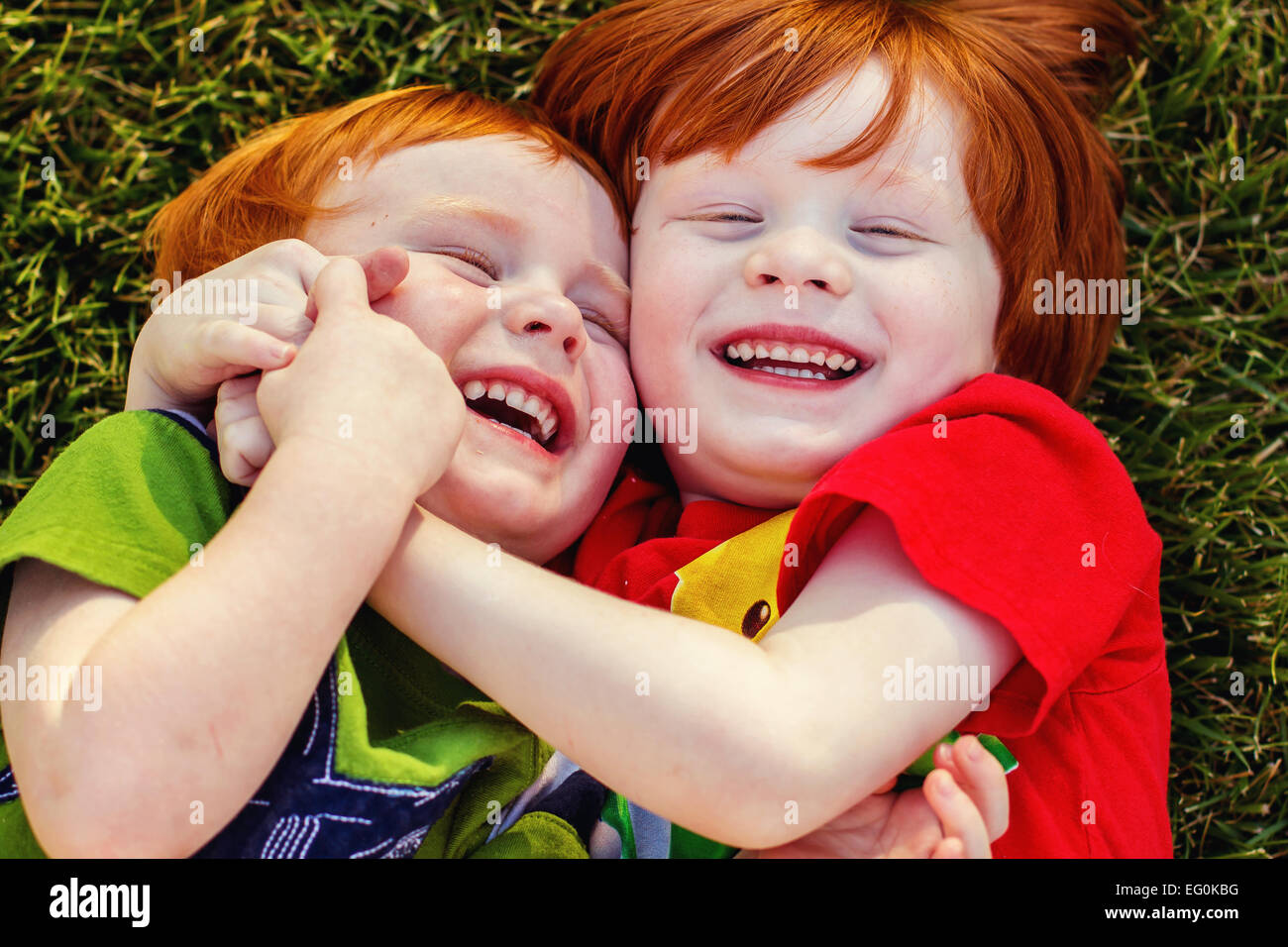 Two happy boys lying on grass laughing - Stock Image