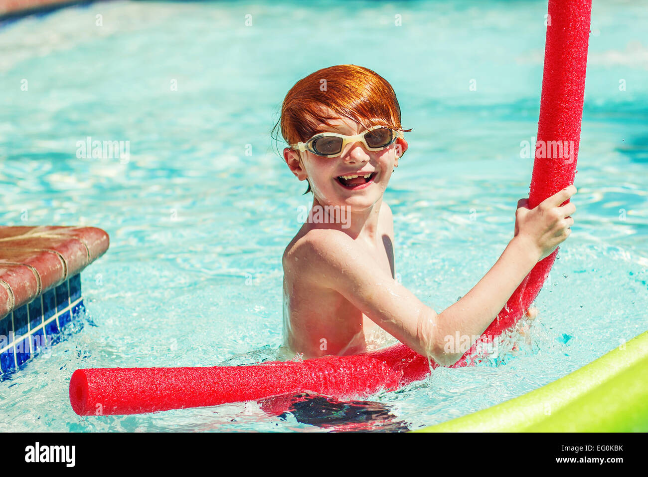 Young boy (6-7) playing in swimming pool - Stock Image