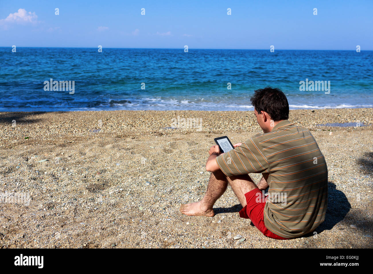 Greece, Thessaloniki, Man reading e-reader on beach - Stock Image