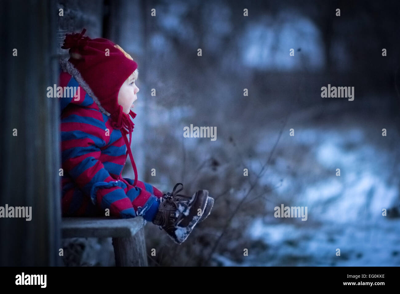 Young boy sitting on bench outside - Stock Image