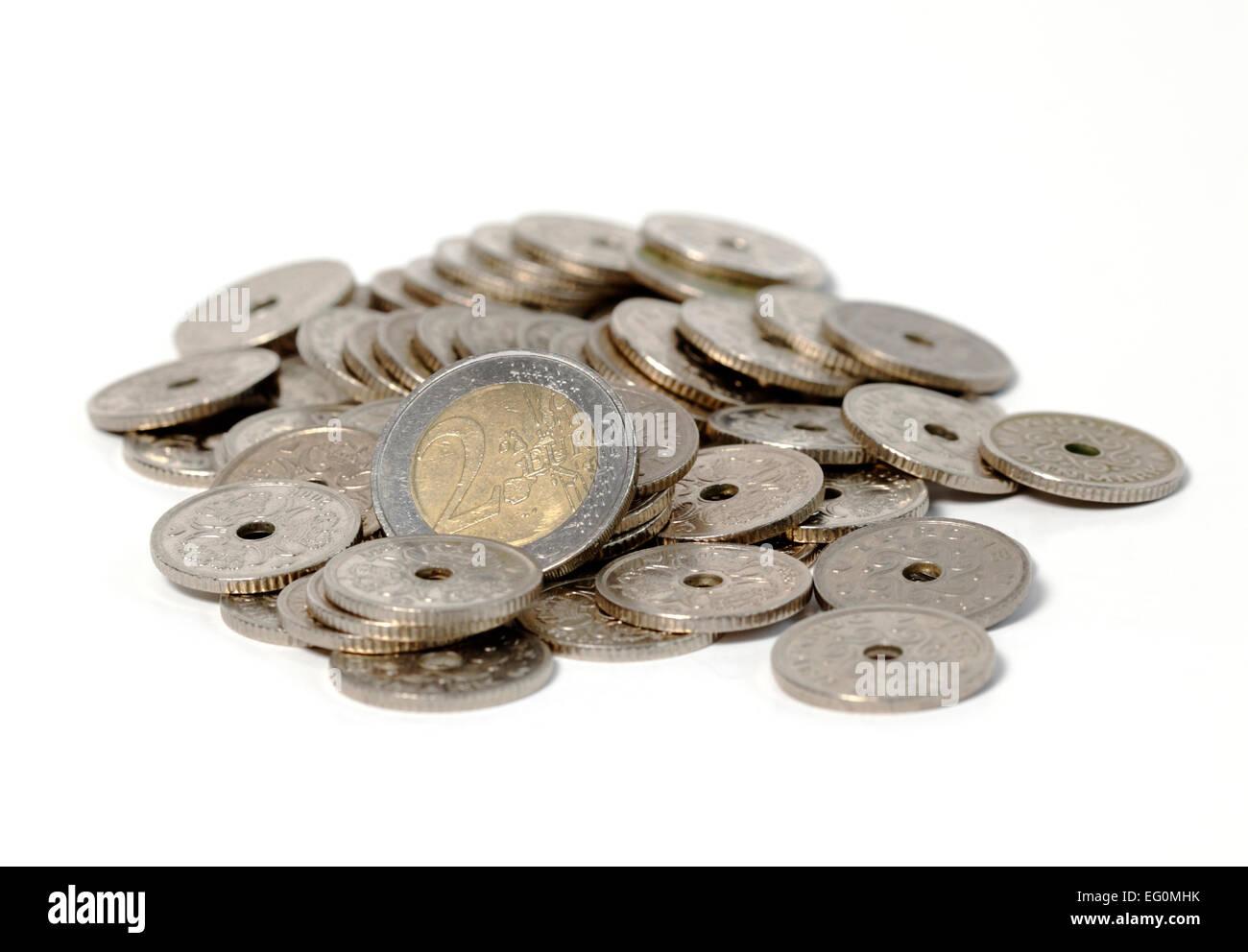 Euros balancing in the midst of Danish Kroner. A 2 Euro coin in the midst of Danish one Krone pieces on white. - Stock Image