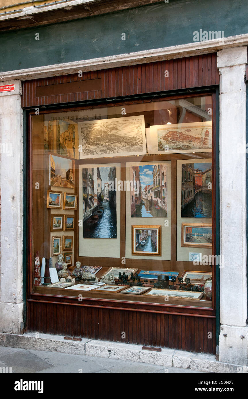 Shop window offering art works paintings pictures for sale on Calle Larga XXII Marzo Venice Italy - Stock Image