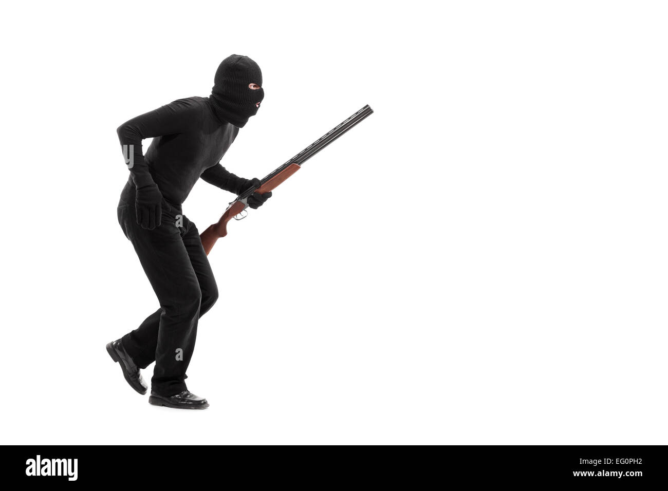 Stealthy criminal with a mask and a rifle walking isolated on white background - Stock Image