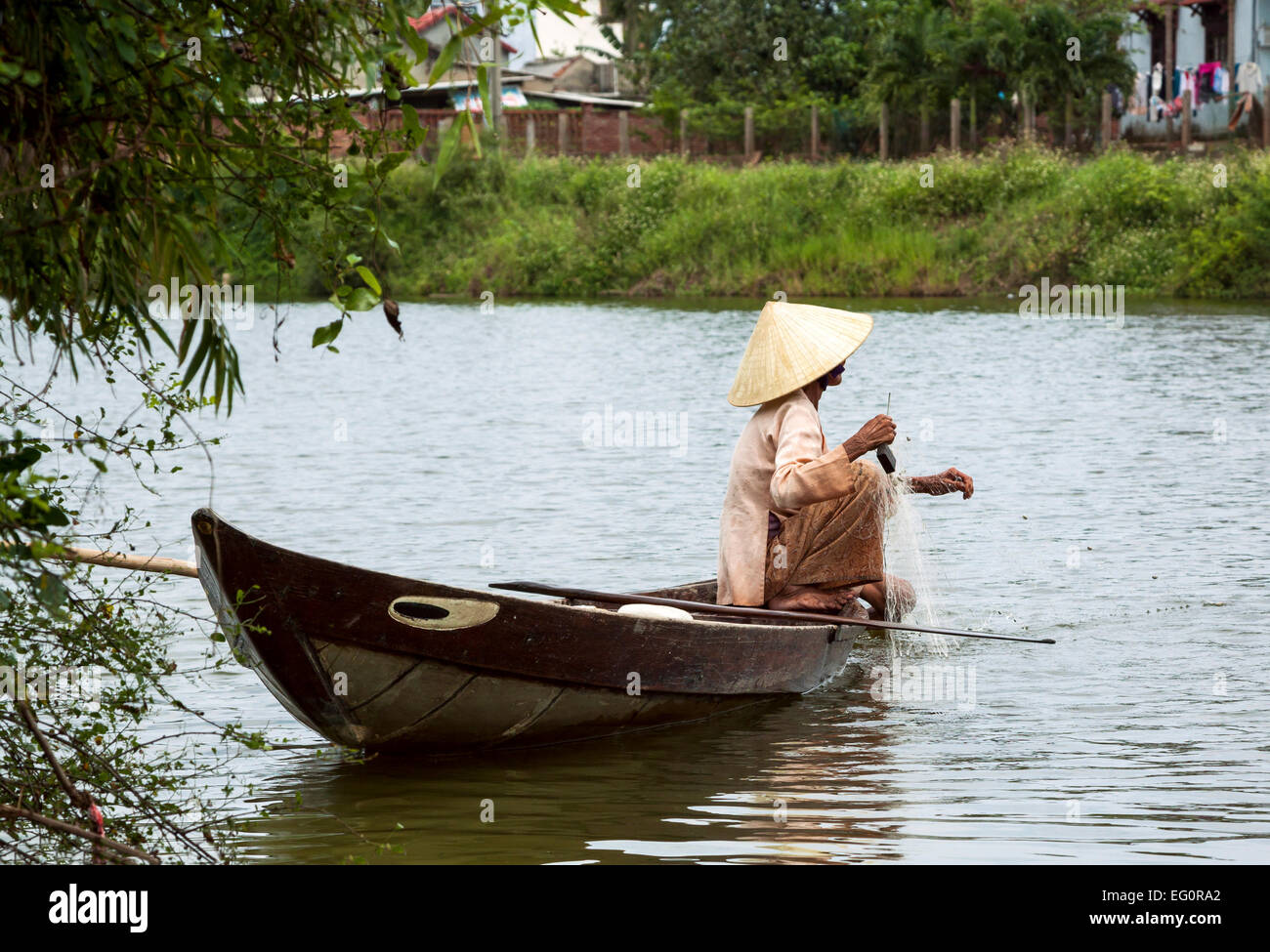 Traditionally dressed old woman fishing from her small fishing boat, Hoi  An, Vietnam, Indochina, Southeast Asia, Asia.
