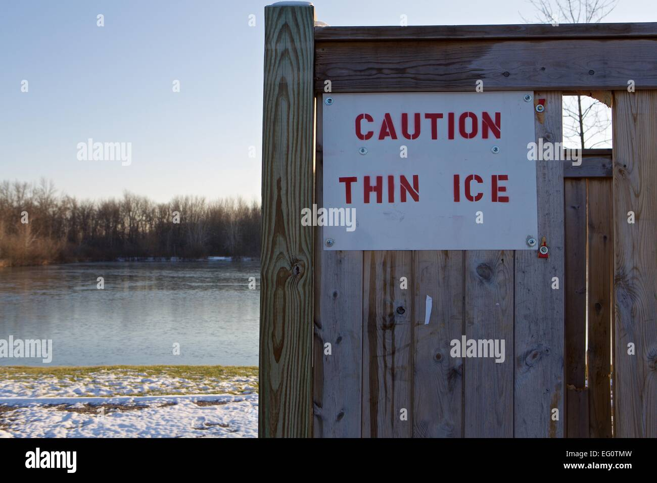 sign warning of thin ice with a lake with snow and ice in the background - Stock Image