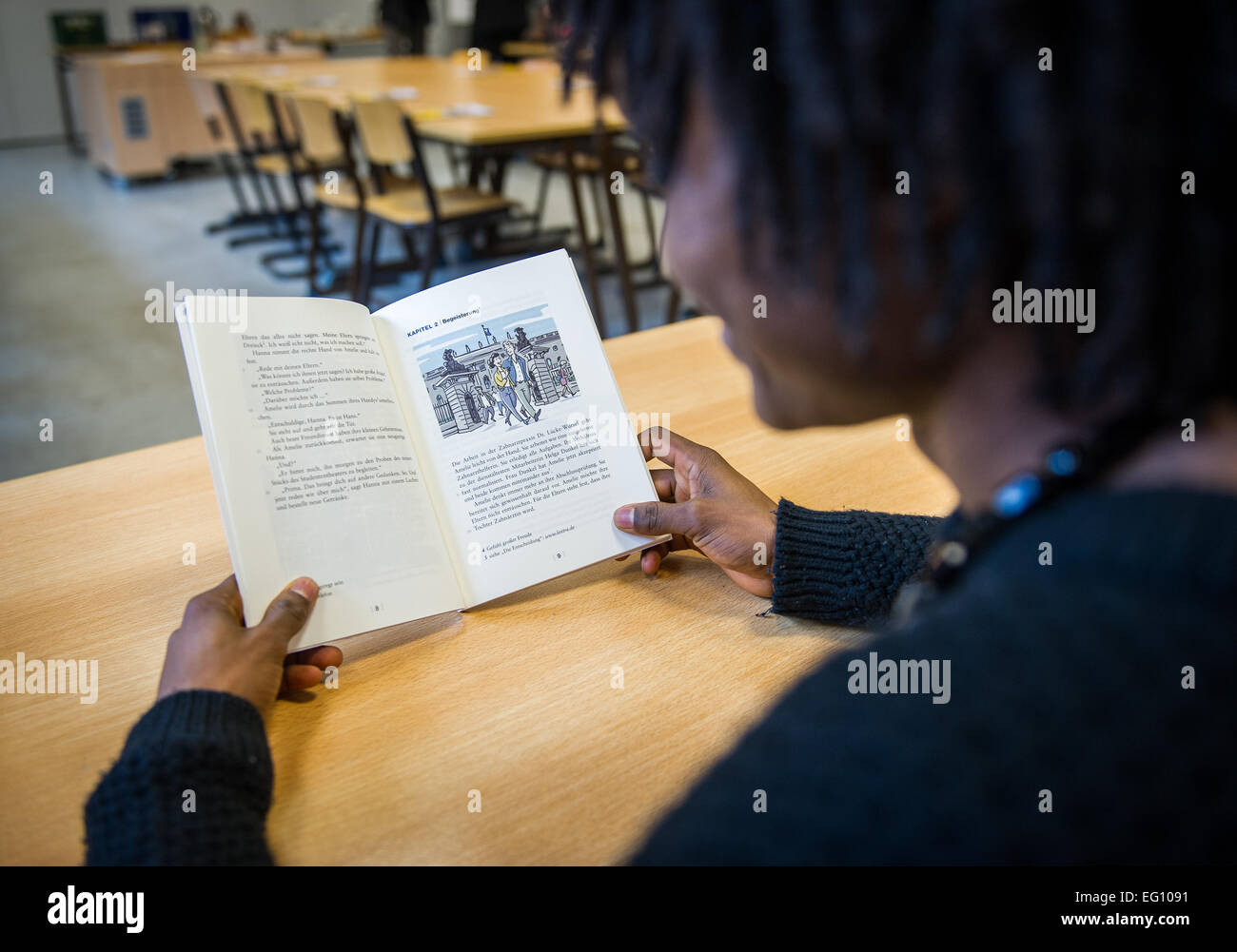 Hanover, Germany. 13th Feb, 2015. A young refugee from Liberia reads a German textbook at a vocational school in - Stock Image
