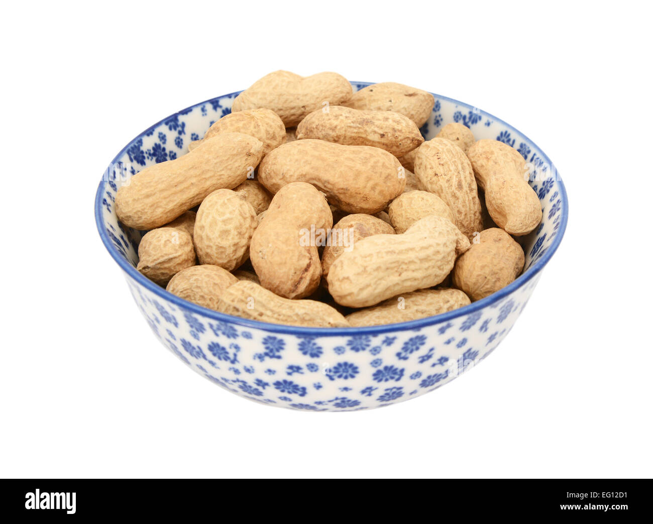 Monkey nuts in a blue and white porcelain bowl with a floral design, isolated on a white background - Stock Image
