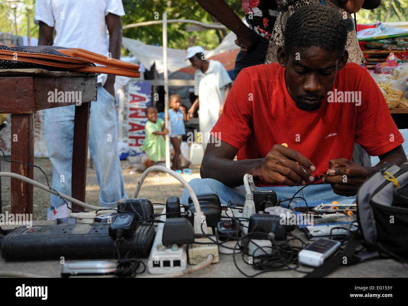 A displaced Haitians man fixes mobile phones in a tent city near, the Presidential Palace in Port au Prince, Haiti Stock Photo