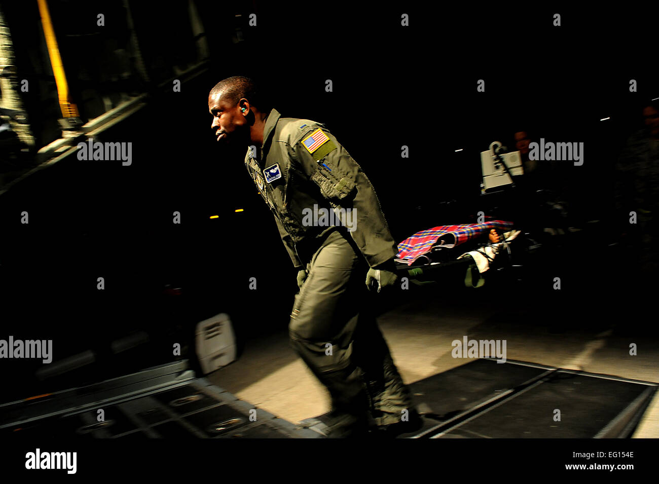 C-130 Navigator Jonathan Lipsey from the 908th Air Lift Wing, Maxwell AFB, AL, by helps load earthquake patients - Stock Image