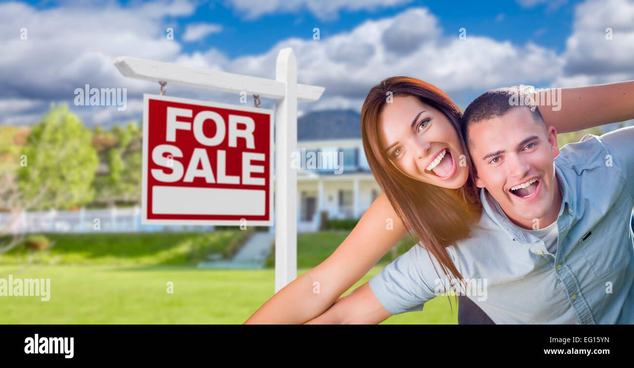 Playful Excited Military Couple In Front of Home with For Sale Real Estate Sign. - Stock Image