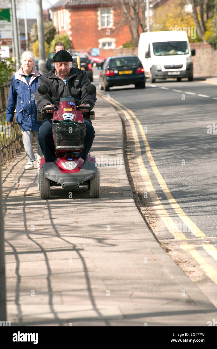 Man riding invalid carriage on pavement - Stock Image