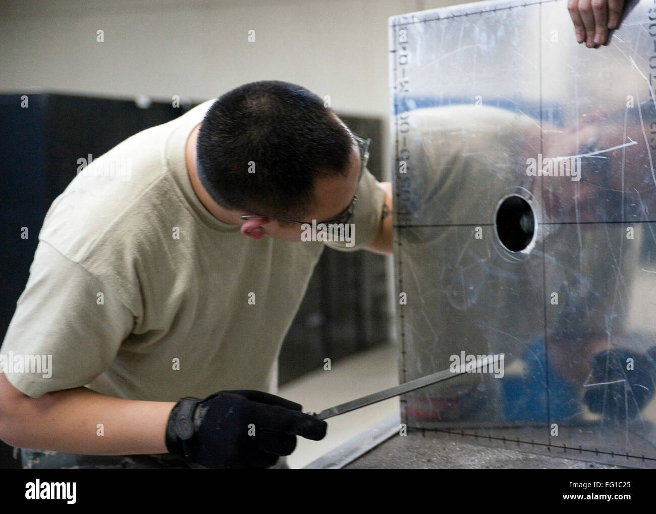 YOKOTA AIR BASE, Japan – Senior Airman Thompson Kongmany, 374th Maintenance Squadron metals technician, examines - Stock Image