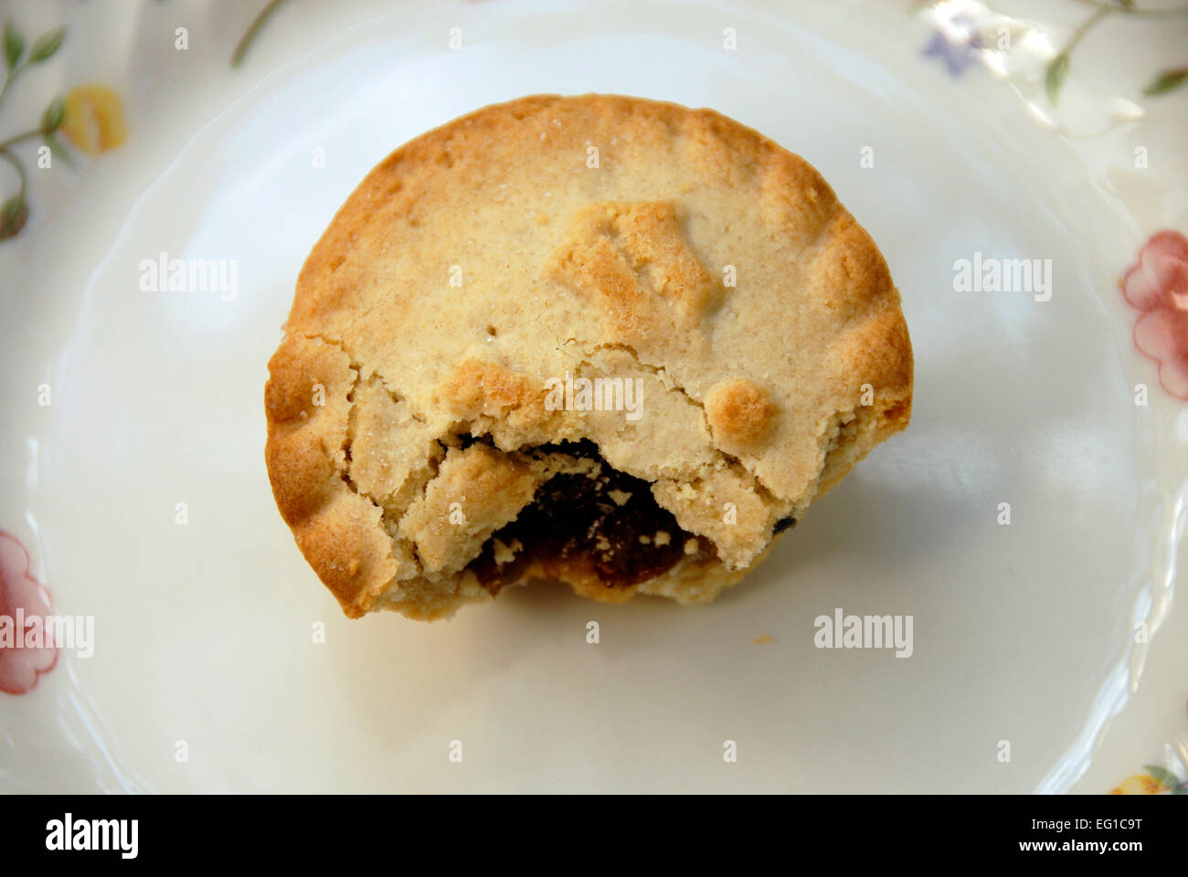 Partly eaten mince pie on plate - Stock Image