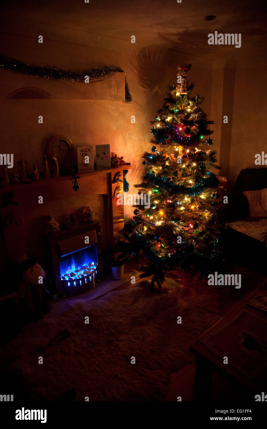 decorated christmas tree with lights on in a darkened room with blue flame effect fire