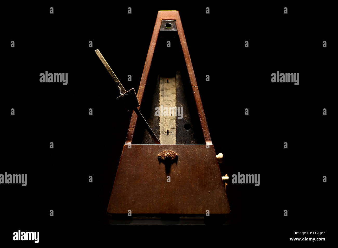Vertical shot of a vintage metronome, on a black background. - Stock Image