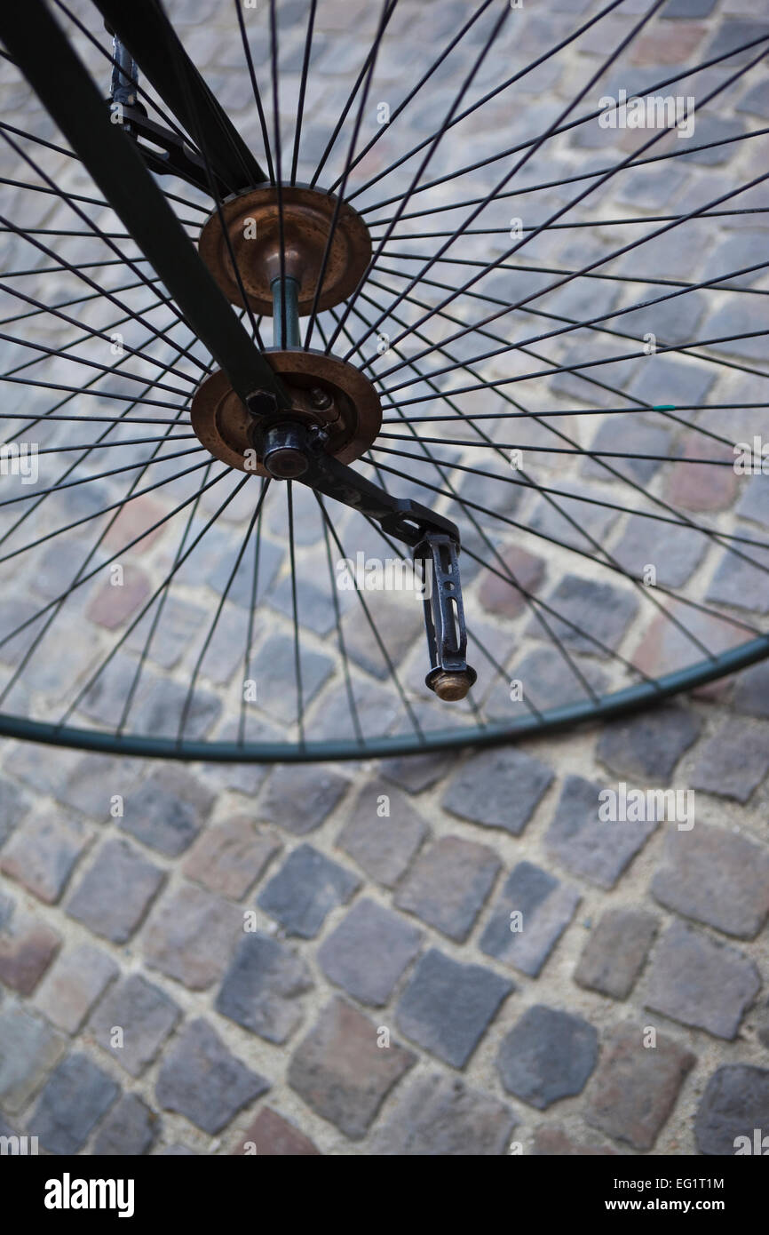 Metal wheel of an old velocipede on a cobbled square - Stock Image