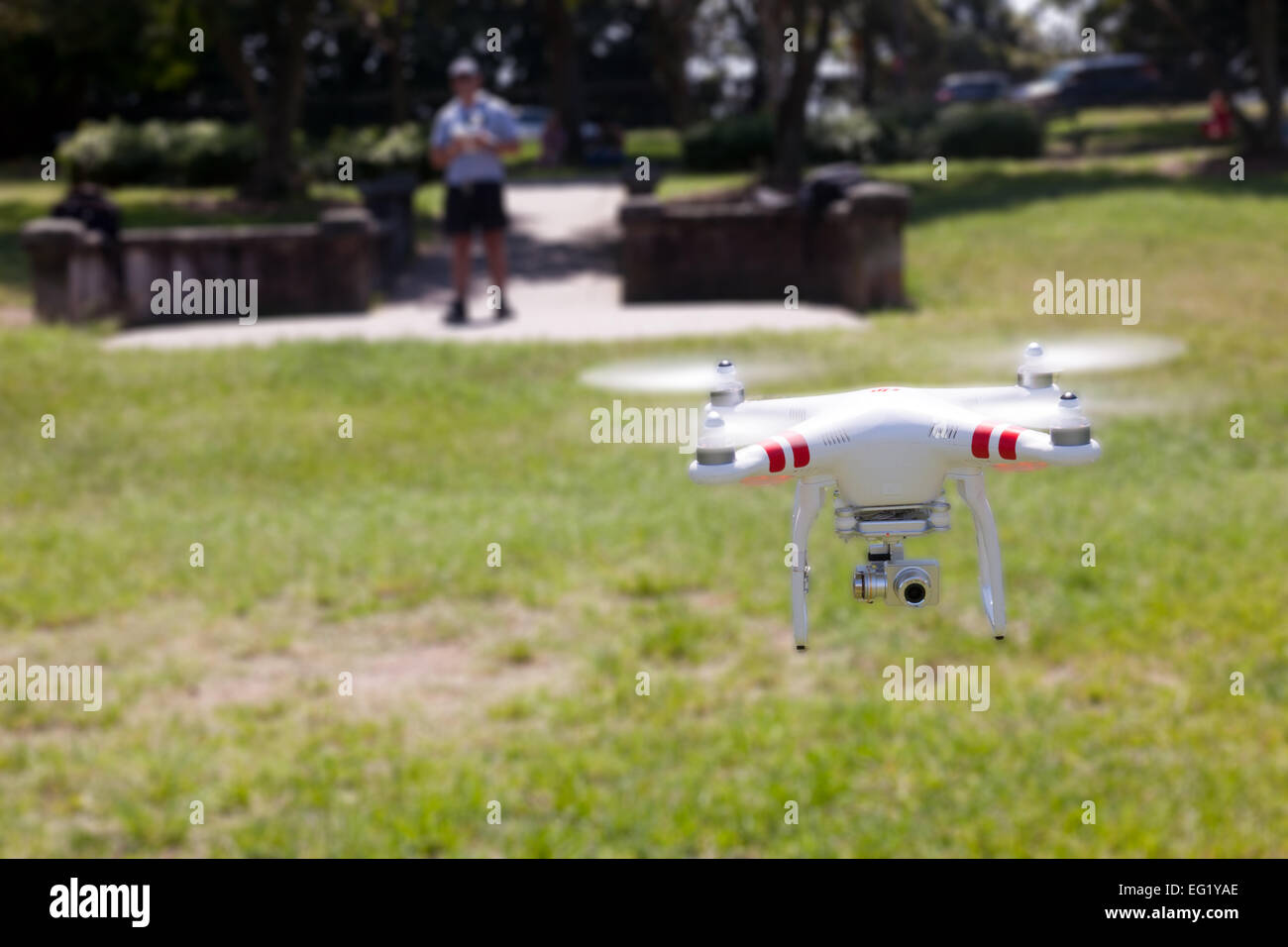 A flying drone with a gimbal and camera attached. With the photographer in the background. - Stock Image
