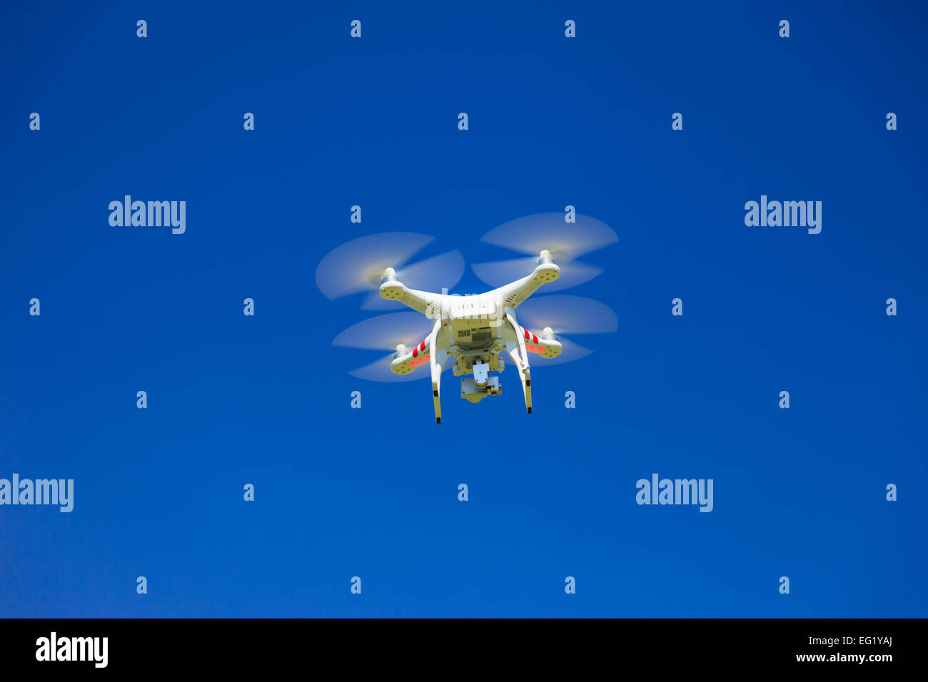 A view from below of a flying drone with a gimbal and camera attached. Drone, photography, flying, surveillance - Stock Image