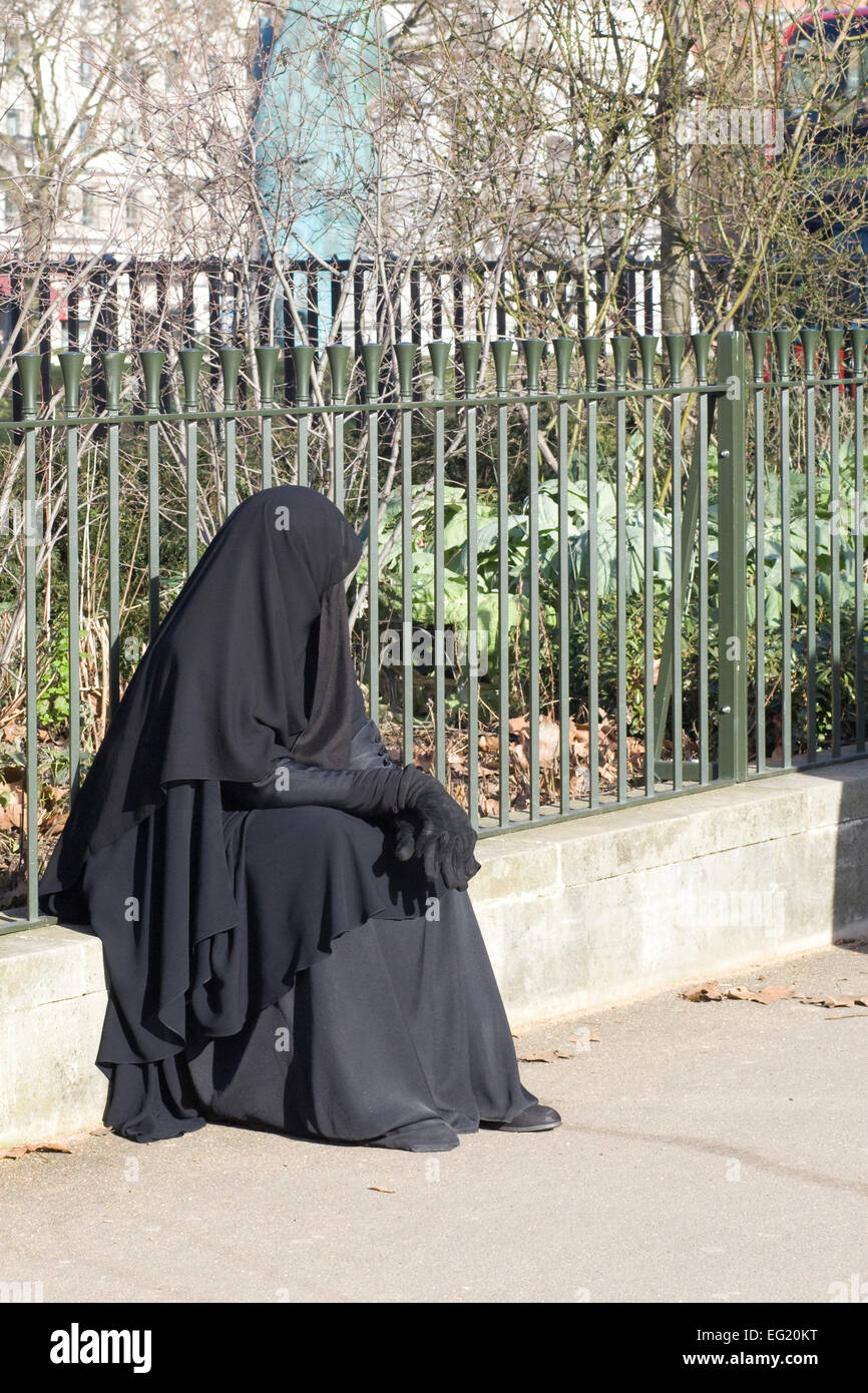 Muslim woman in a Burka sitting on the curb in London england - Stock Image