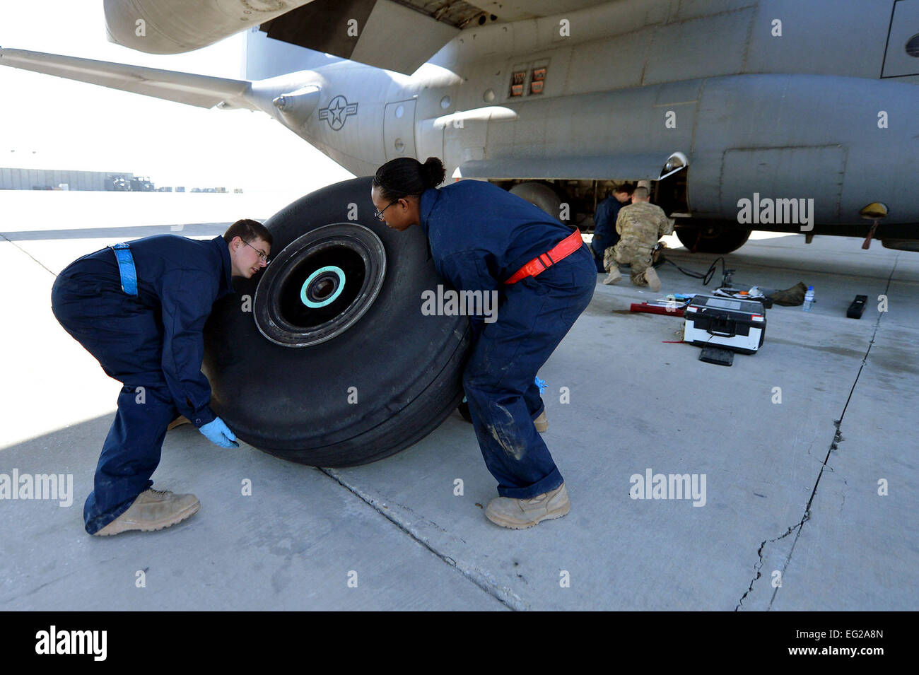 Crew chiefs assigned to the 455th Expeditionary Aircraft Maintenance Squadron replace a tire on a C-130 Hercules, March 6, 2013, on Bagram Airfield, Afghanistan. The crew is deployed from Little Rock Air Force Base, Ark. Senior Airman Chris Willis Stock Photo