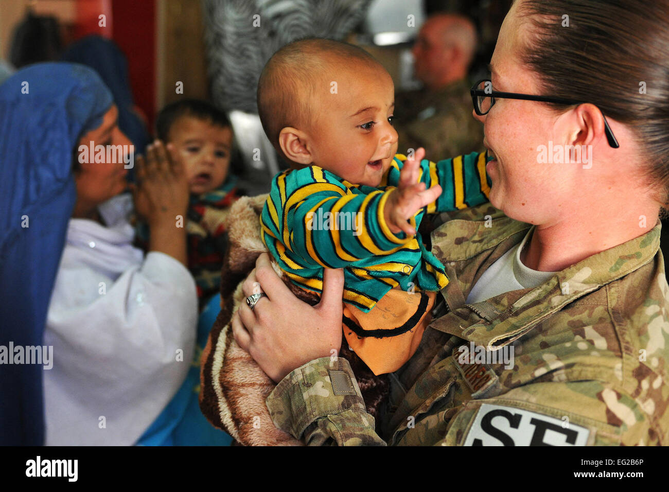 Airman 1st Class Riostasia Johns, 455th Expeditionary Security Forces Squadron entry controller, holds an Afghan baby while her mother processes through the medical entry control point on April 16 at Bagram Airfield, Afghanistan.  Senior Airman Chris Willis Stock Photo