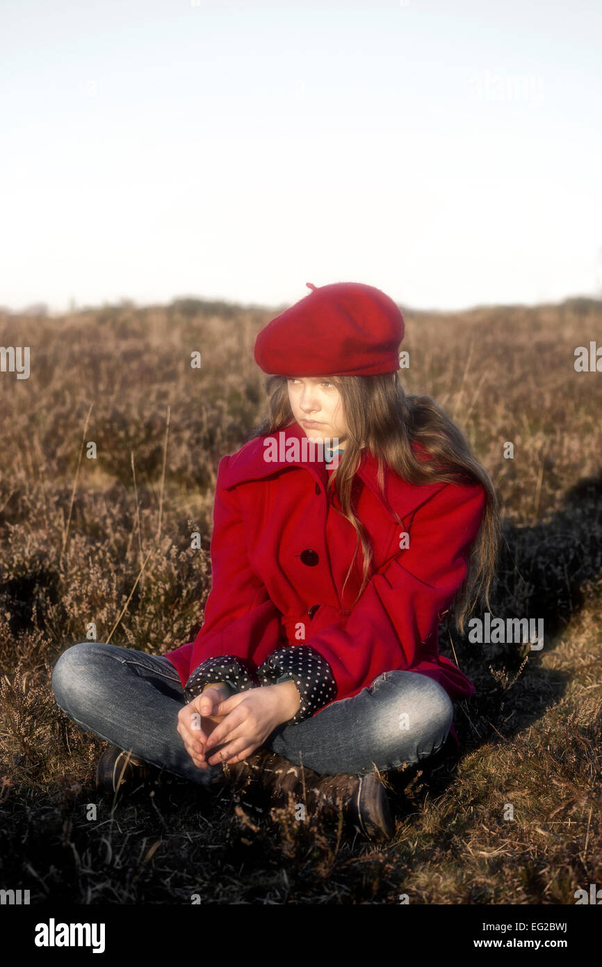 a girl in a red coat is sitting on a hill - Stock Image