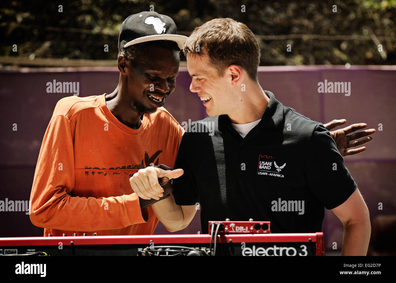 Senior Airman Mike Mitchell laughs with a Senegalese musician during a concert June 14, 2014, at a local cultural - Stock Image