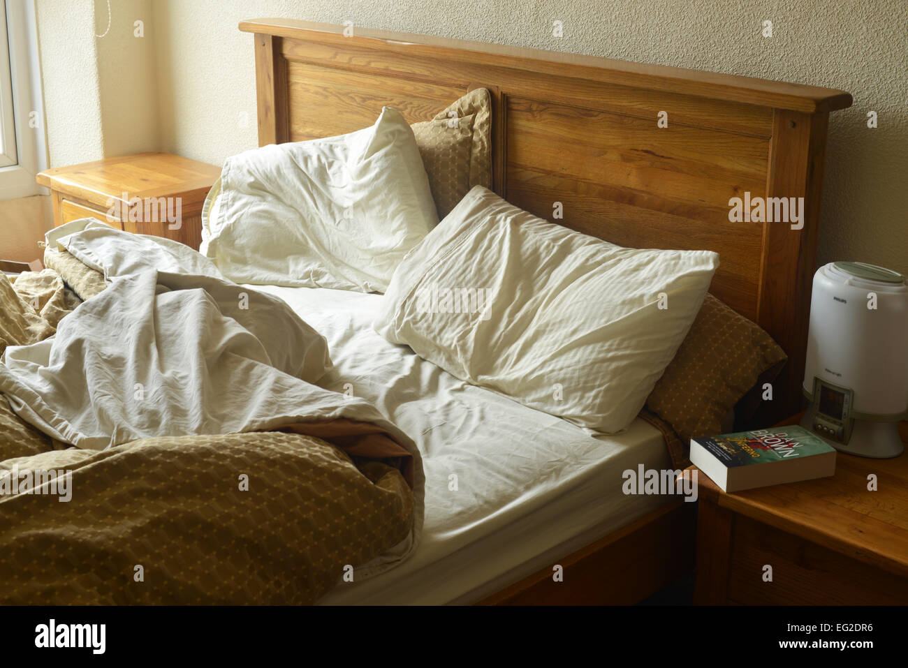 An unmade double bed. - Stock Image