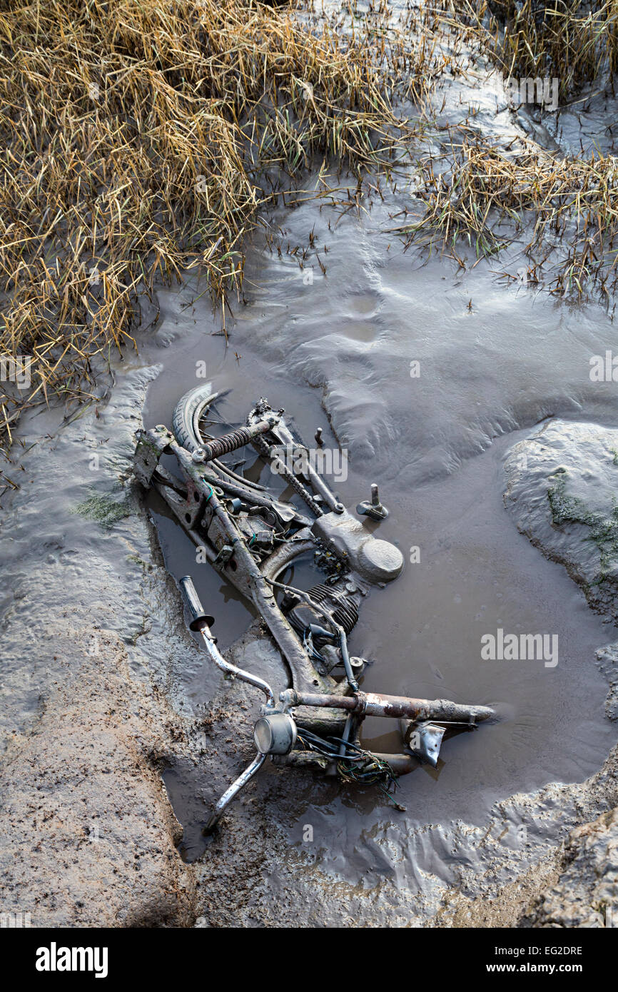 Motor cycle dumped in the mud at low tide, Beachley Point, River Severn, Gloucestershire, England, UK - Stock Image