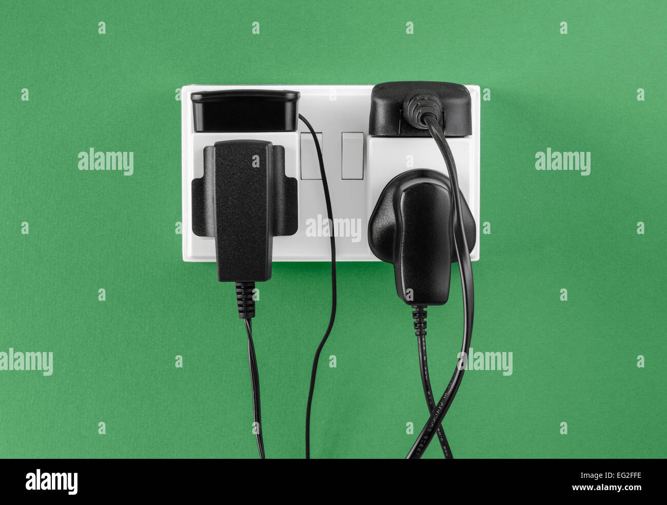 Battery chargers plugged in to outlet - Stock Image