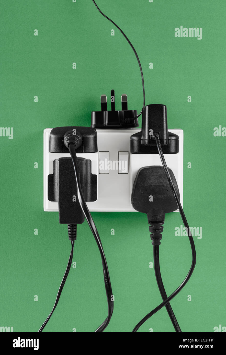 Multiple Chargers plugged in to Wall Socket - Stock Image