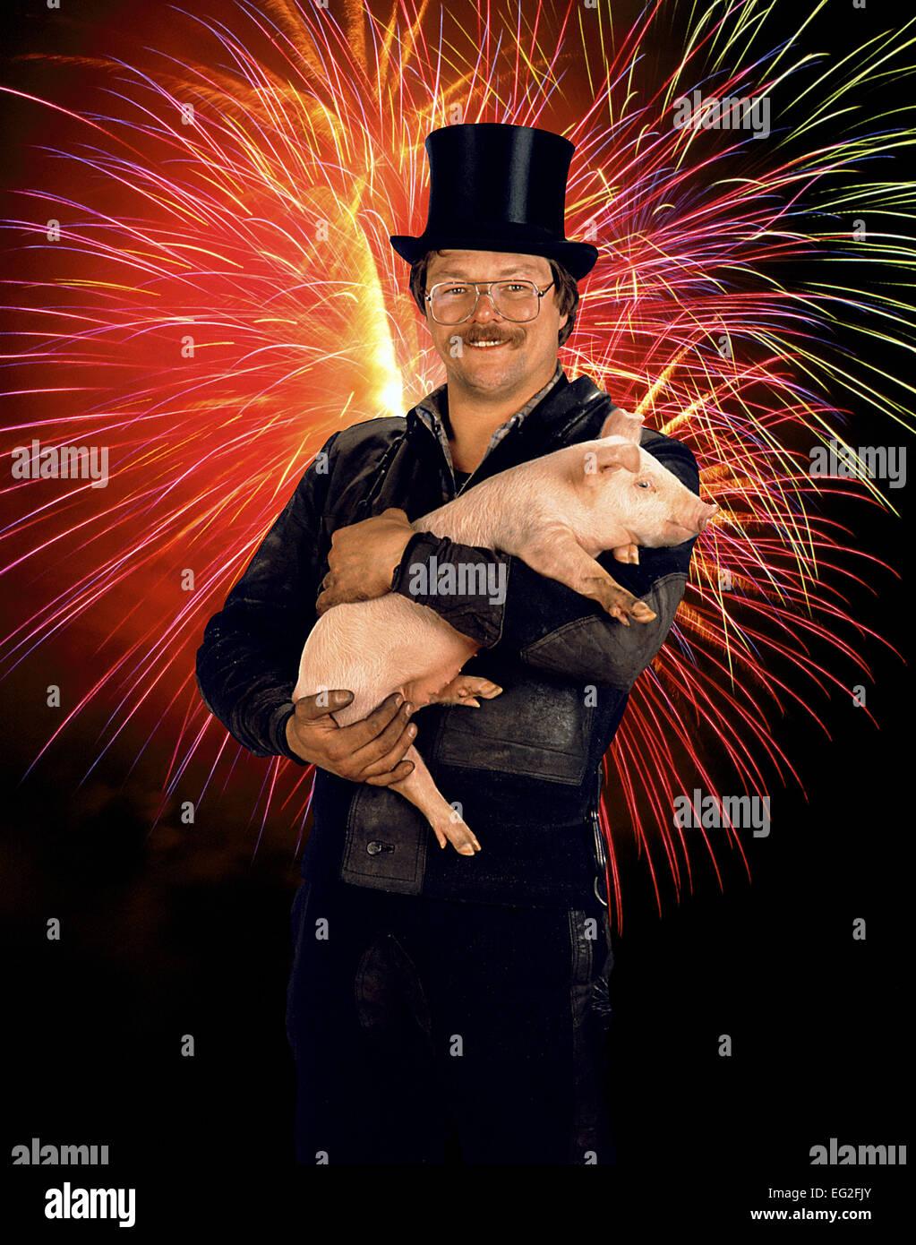 Gluecksbringer Kaminkehrer Schornsteinfeger haelt ein Schwein Ferkel auf dem Arm Feuerwerk Sylvester Neujahr Jahreswechse - Stock Image