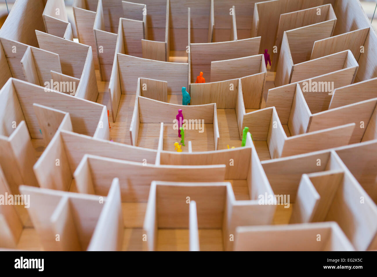 Miniature human figures in architectural model of maze - Stock Image