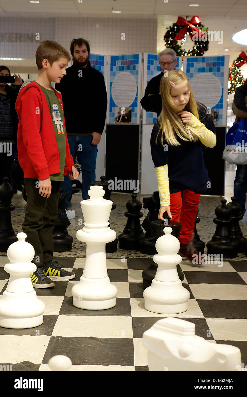 10 years old girl and boy play chess in public with large garden plastic chess set.  Nordstan, Göteborg, Sweden - Stock Image