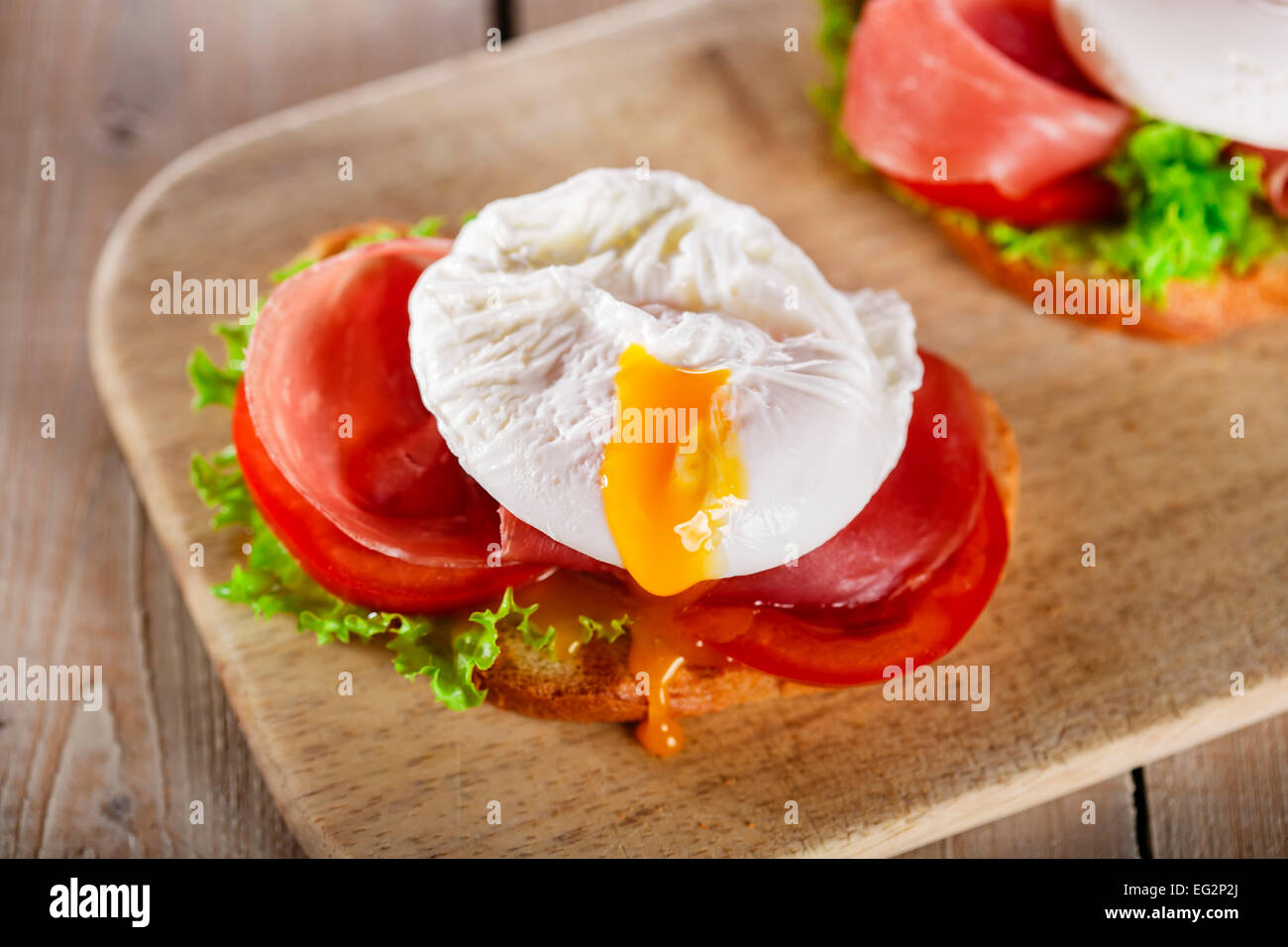 sandwich with prosciutto and poached egg tomato - Stock Image
